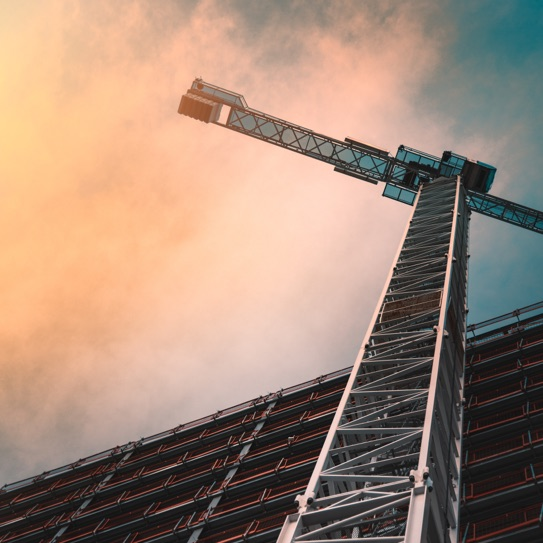 Photo of a crane from below with orange coloured clouds in the sky